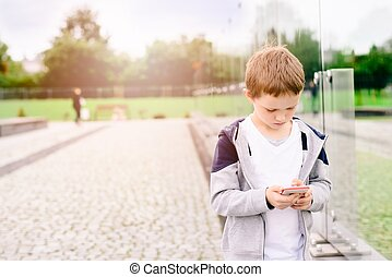 Little boy child playing mobile games on smartphone in the...