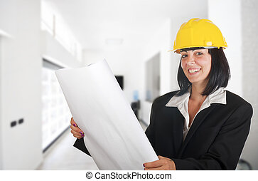 young architect woman with floor plan of a building
