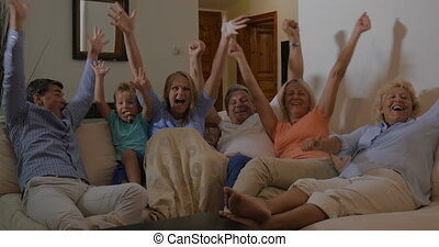 Family watching sport event on TV and happy with victory -...