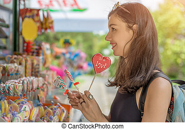 Smiling beautiful young woman with lollipops - Portrait of...