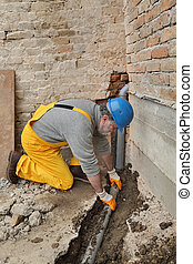 Plumber at construction site installing sewerage tube