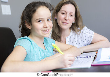 Mature mother helping her child with homework at home.