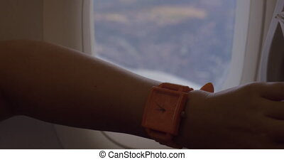 Woman in the plane setting watch backward - Close-up shot of...