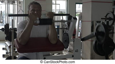 Senior man exercising on bicep training machine - Senior man...