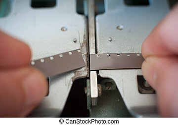 Super 8 movie editing hands connecting filmstrip closeup in...