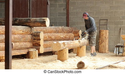 Man cuts off beam chainsaw for future log cabin....