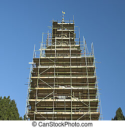 Scaffold around church spire with a blue sky background