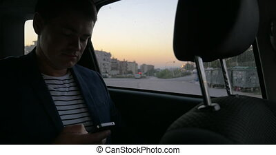 Man in car browsing the internet on smart phone