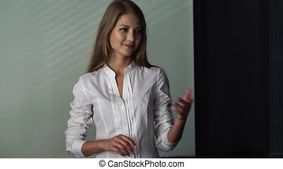 Beautiful makeup blond woman in white shirt holding and presenting something in the hand with happy smiling