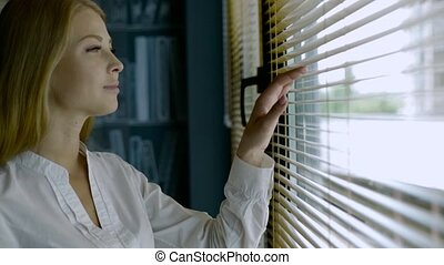 Close-up of cute blonde woman looking through out the blinds