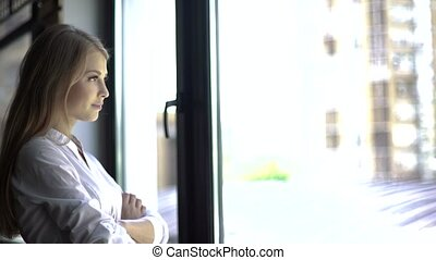 Close-up portrait of confident woman in white shirt standing with arms crossed and thinking near window.