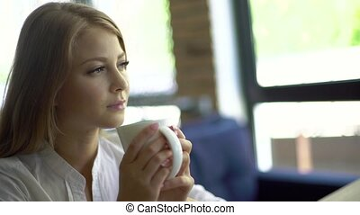 Young thoughtful beautiful woman holding coffee cup and...