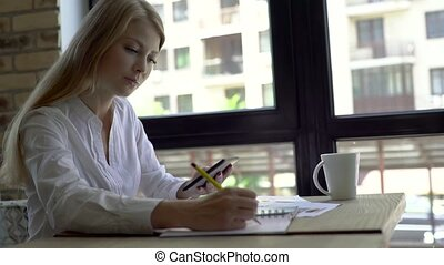 Serious young woman with a cup of coffee, notepad and tablet at cafe. Freelancer