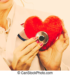 Doctor with stethoscope examining red heart. - Medical...