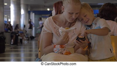 Mother and son with cellphone in airport lounge