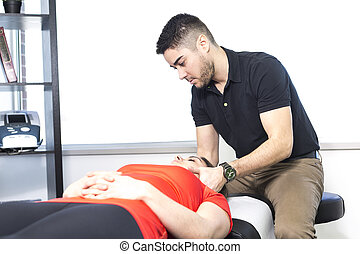 woman lying while being massaged by a man in room - A woman...