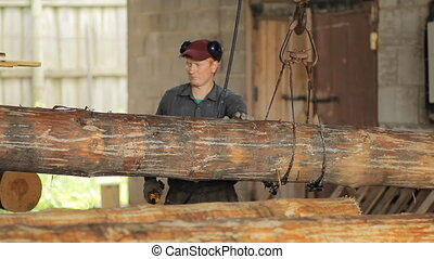Man raises a wooden beam on the crane in a hangar. Work...
