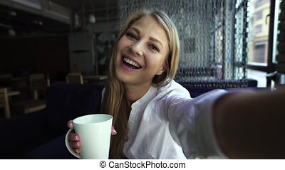 Pretty blonde woman taking self portrait while drinking...