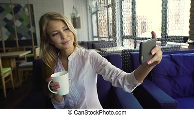 An attractive young blonde woman taking a self portrait on...