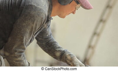 Man working with a chainsaw. Wood shavings are flying saw...