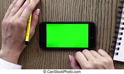 Female hand using smart phone or cellphone with pencil and...