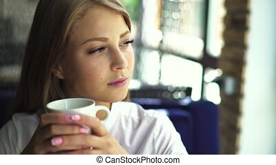 Beautiful blonde girl with nude make up wearing white blouse, sitting in cafe with cup of coffee looking away and at the camera