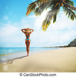 Tropical holiday - Girl with straw hat walking on the beach...