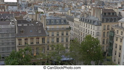 Flock of pigeons flying in Paris - View to Paris with...