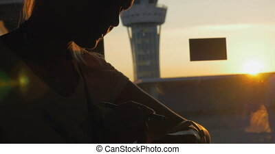 Woman with smart watch in airport at sunset