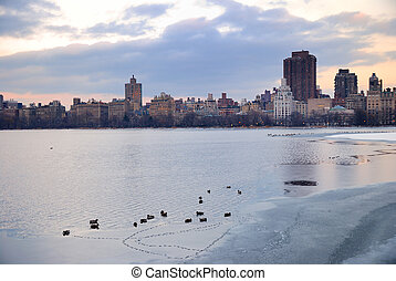 Central Park lake with New York City Skyline in winter with...