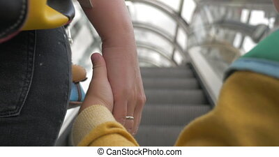 Mother and son holding hands while riding escalator -...