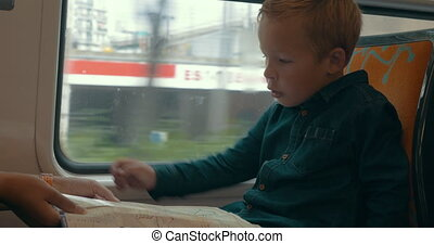 Child looking at map in the train - Boy learning to use map....