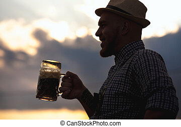 Happy smiling man tasting fresh brewed beer against the sky...