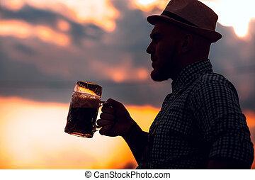 Happy smiling man tasting fresh brewed beer against the sky...