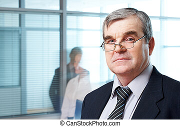 Serious boss - Portrait of mature boss in eyeglasses looking...