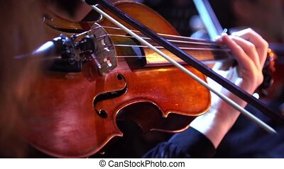 Concert, a woman playing the violin, hand close up