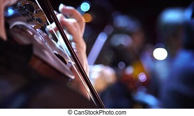 Concert, a musician hand playing the violin, close up shot -...