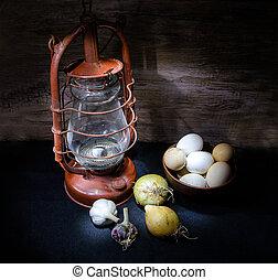 kerosene lamp and eggs with vegetables in dark