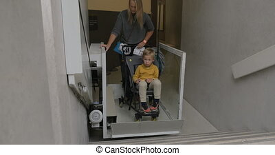 Woman and child using lift for carriages - Mother and son in...