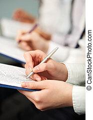At seminar - People make notes in documents at seminar