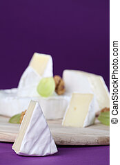 Camembert cheese on cutting board with walnuts and grapes