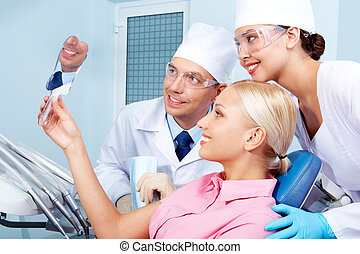 In dental clinic - Image of patient holding mirror with...