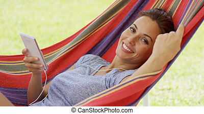 Happy young woman listening to music in a hammock