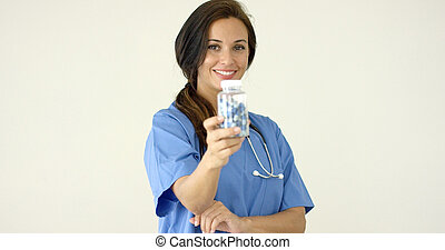 Young brown haired doctor in scrubs holds bottle towards...
