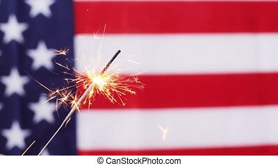 close up of sparkler burning over american flag - american...