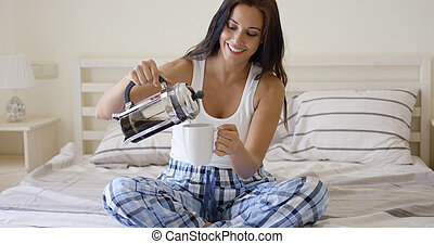 Happy young woman pouring herself coffee - Happy young woman...