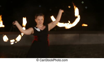 Fire show in the night - Woman twist fiery circles on a fire...