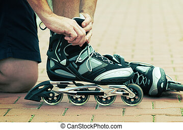 Man preparing for roller blading, putting on rollerblades