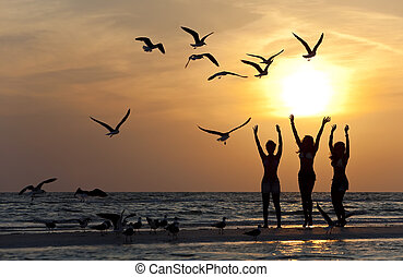 Three Young Women Dancing On Beach At Sunset