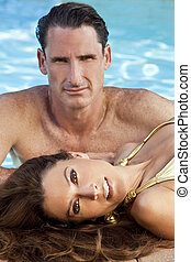 Beautiful Couple Relaxing By Swimming Pool - Portrait of a...